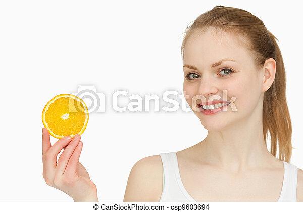 Cheerful woman holding an orange slice - csp9603694