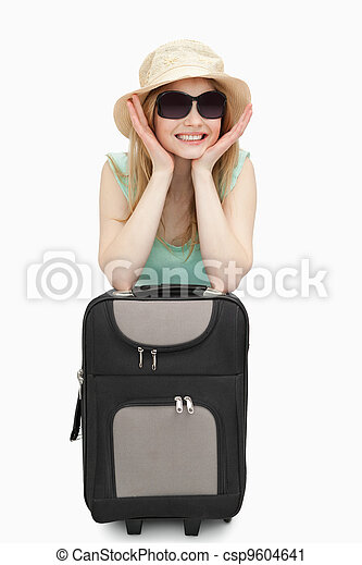 Cheerful woman leaning on a suitcase while sitting - csp9604641