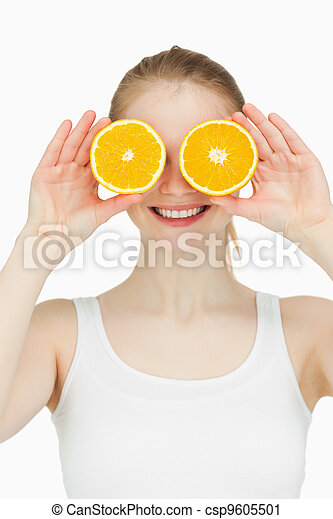 Cheerful woman placing oranges on her eyes - csp9605501