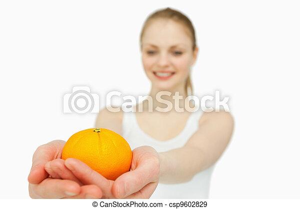 Cheerful woman presenting a tangerine - csp9602829