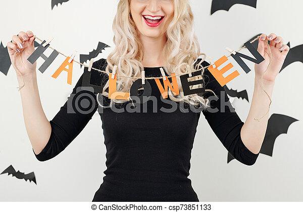 Cheerful woman showing Halloween garland - csp73851133