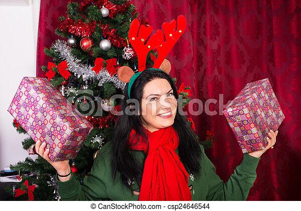 Cheerful Xmas woman showing gifts - csp24646544