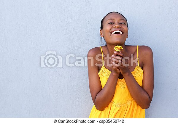 Cheerful young african woman holding a flower - csp35450742