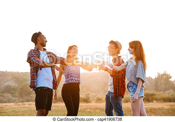 Cheerful young friends drinking beer and soda outdoors - csp41906738