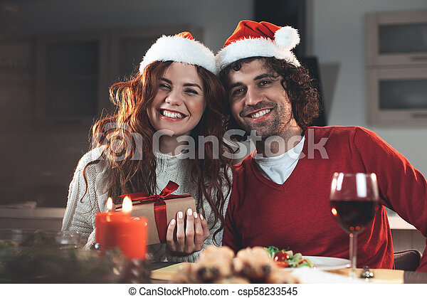Cheerful young man and woman celebrating winter holiday - csp58233545