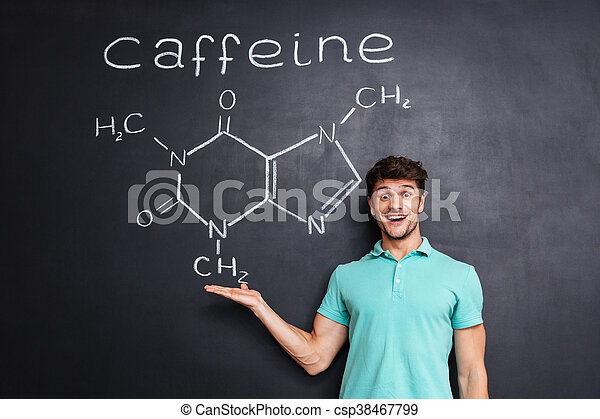 Cheerful young scientist showing chemical structure of caffeine molecule - csp38467799