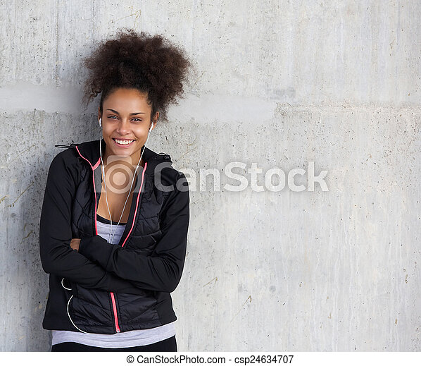 Cheerful young sports woman smiling on gray background - csp24634707