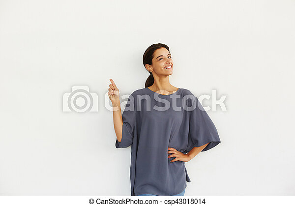 Cheerful young woman pointing at copy space - csp43018014