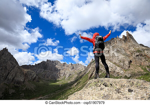 cheering woman with backpack hiking in mountains - csp51907979