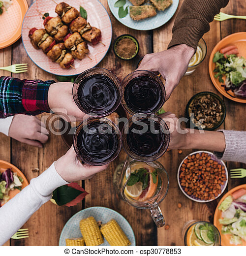 dinner table top view. dining table · cheers to friends! top view of four people cheering with red wine while sitting at dinner