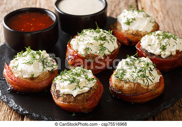 Cheese stuffed mushrooms wrapped in bacon served with sauces close-up on a plate. horizontal - csp75516968