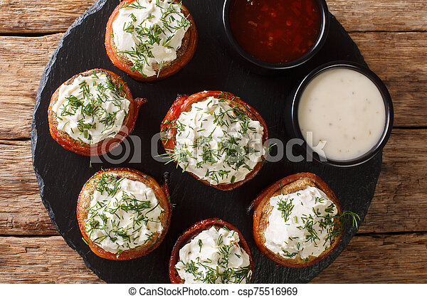 Cheese stuffed mushrooms wrapped in bacon served with sauces close-up on a plate. horizontal top view - csp75516969