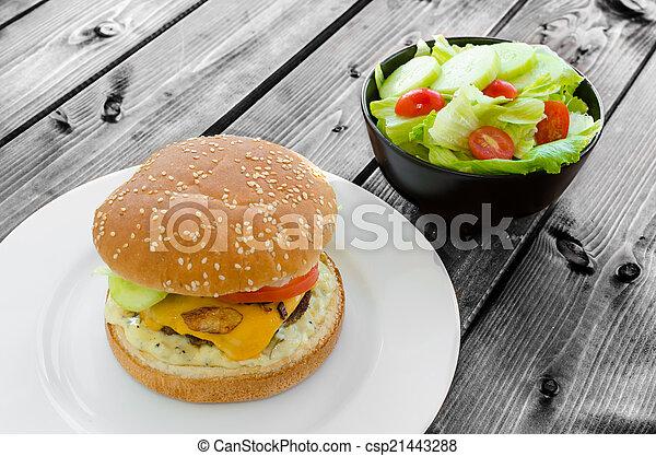 Cheeseburger with bacon and tartar sauce and garden salad - csp21443288