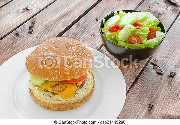 Cheeseburger with bacon and tartar sauce and garden salad - csp21443290