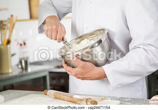 Chef Mixing Batter With Wire Whisk In Bowl In Kitchen - csp24471154