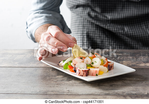 Chef preparing seafood ceviche on wooden table - csp44171001