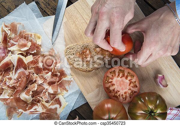 Chef rubbing tomato on a slice of bread - csp35450723