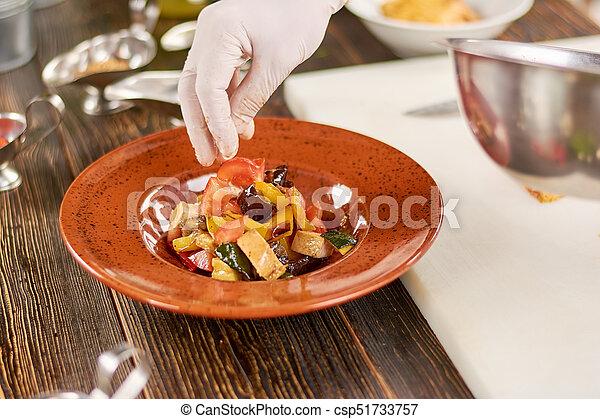 Chef mano sprinkling sal en la ensalada. - csp51733757