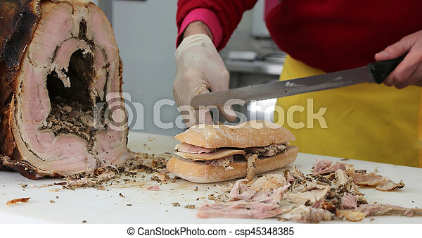 chef slicing the meat of pork to prepare a sandwich in the food - csp45348385