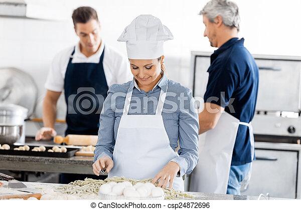 Chefs Preparing Pasta In Kitchen - csp24872696
