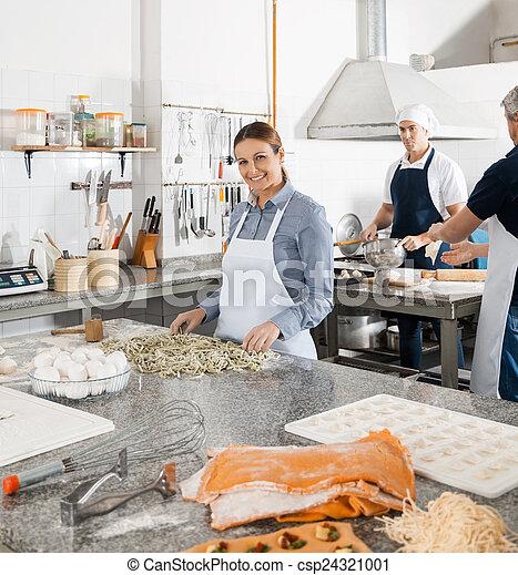 Chefs Preparing Pasta In Kitchen - csp24321001