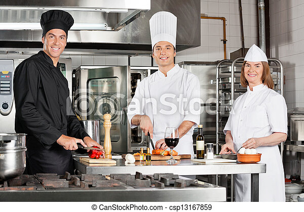 Chefs Working In Industrial Kitchen - csp13167859