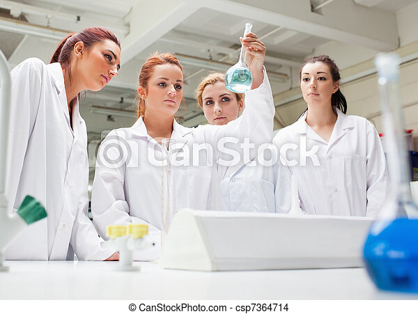 Chemistry students looking at a liquid - csp7364714
