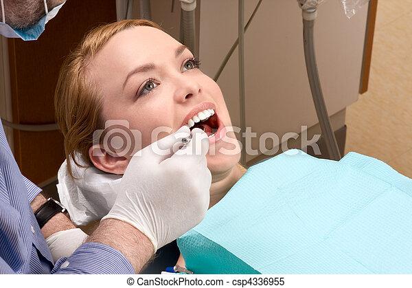 Una joven con la boca abierta durante la revisión dental - csp4336955