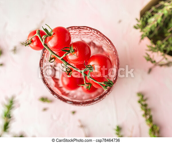 Cherry tomatoes and fresh thyme on a pink background - csp78464736