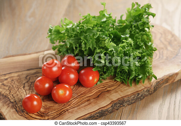 cherry tomatoes and frisee lettuce on cutting board - csp43393567