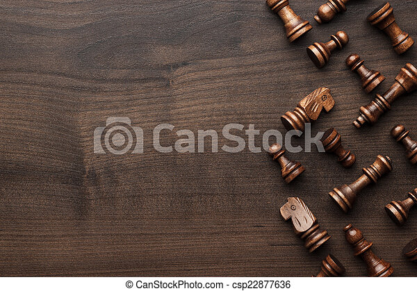 chess figures on brown wooden table background - csp22877636