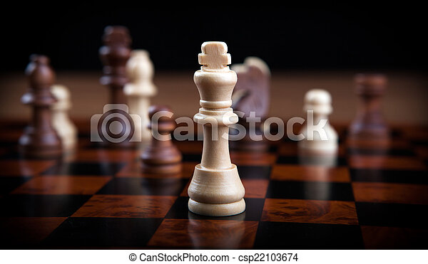 chess pieces lined up in a row on a gray - csp22103674