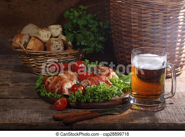 Chicken beaters in bacon submitted on leaves of salad with fresh tomatoes and beer in a transparent mug - csp28899718