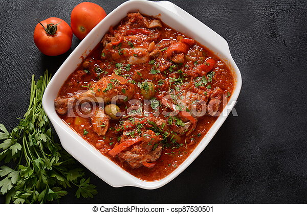 Chicken cacciatore with bell peppers, tomatoes, black olives. Italian food - csp87530501