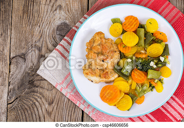 Chicken fillet grilled with vegetable mixt on wooden background - csp46606656