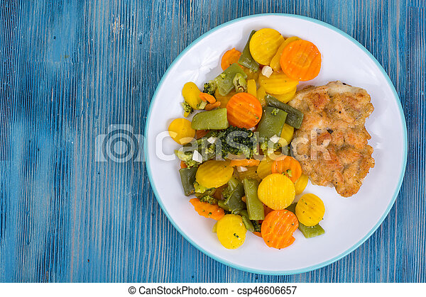 Chicken fillet grilled with vegetable mixt on wooden background - csp46606657
