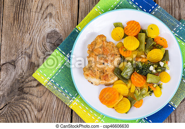 Chicken fillet grilled with vegetable mixt on wooden background - csp46606630
