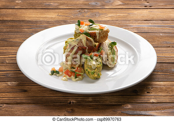 Chicken fillet rolls wrapped in bacon with avocado and vegetable filling - csp89970763