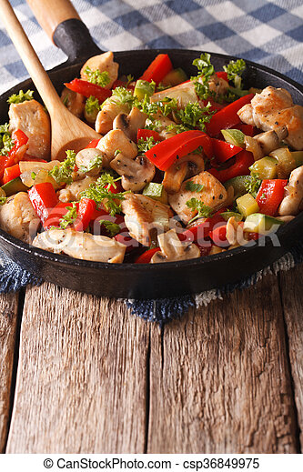 Chicken saute with mushrooms, peppers and zucchini on a frying pan. Vertical - csp36849975