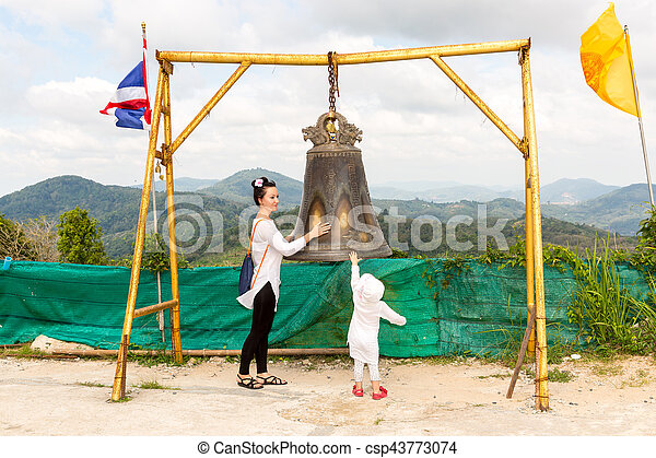 Child and mom near Thai gong in Phuket. Tradition asian bell in Buddhism temple in Thailand. Famous Big bell wish near Gold Buddha - csp43773074