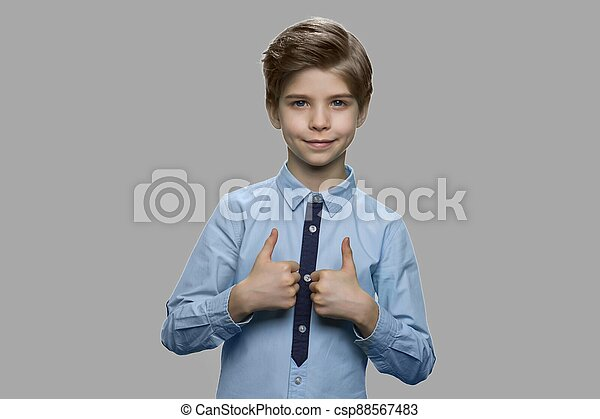 Child boy giving thumbs up against gray background. - csp88567483