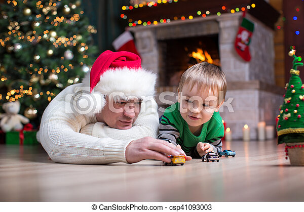 Child boy playing toy cars with his parents under the christmas tree - csp41093003