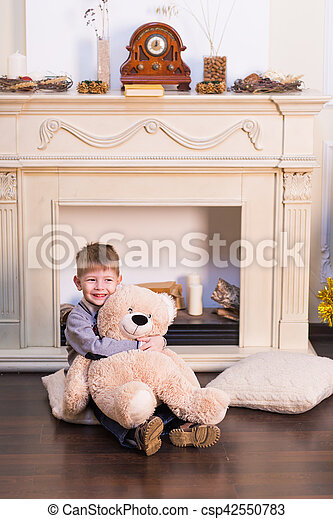 Child boy playing with soft toy bear under the Christmas tree. - csp42550783