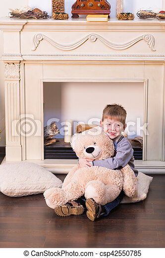 Child boy playing with soft toy bear under the Christmas tree. - csp42550785