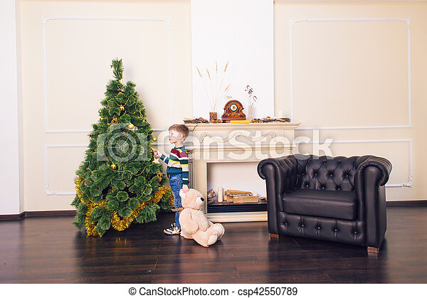 Child boy playing with soft toy bear near the Christmas tree. - csp42550789