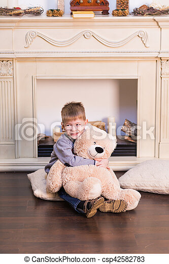 Child boy playing with soft toy bear under the Christmas tree. - csp42582783