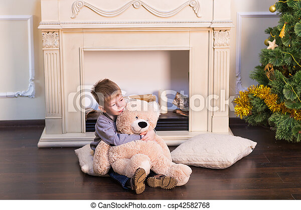 Child boy playing with soft toy bear under the Christmas tree. - csp42582768