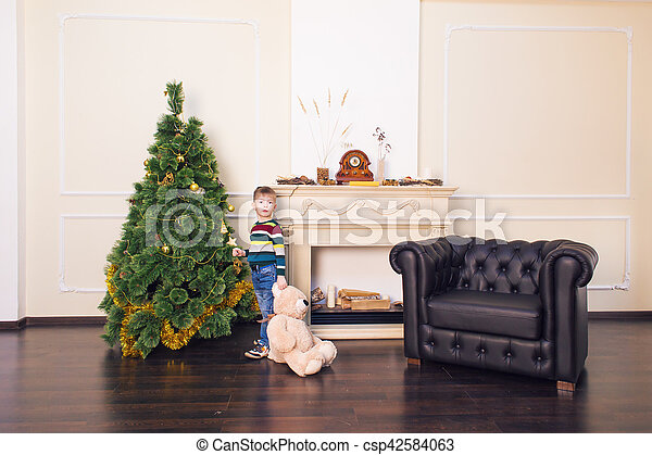 Child boy playing with soft toy bear near the Christmas tree. - csp42584063