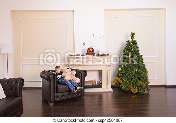 Child boy playing with soft toy bear near the Christmas tree. - csp42584067