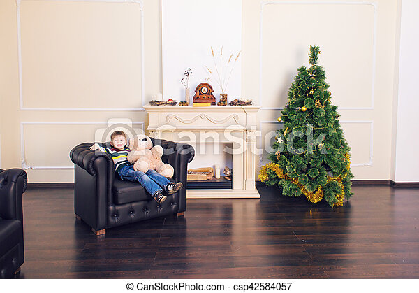 Child boy playing with soft toy bear near the Christmas tree. - csp42584057